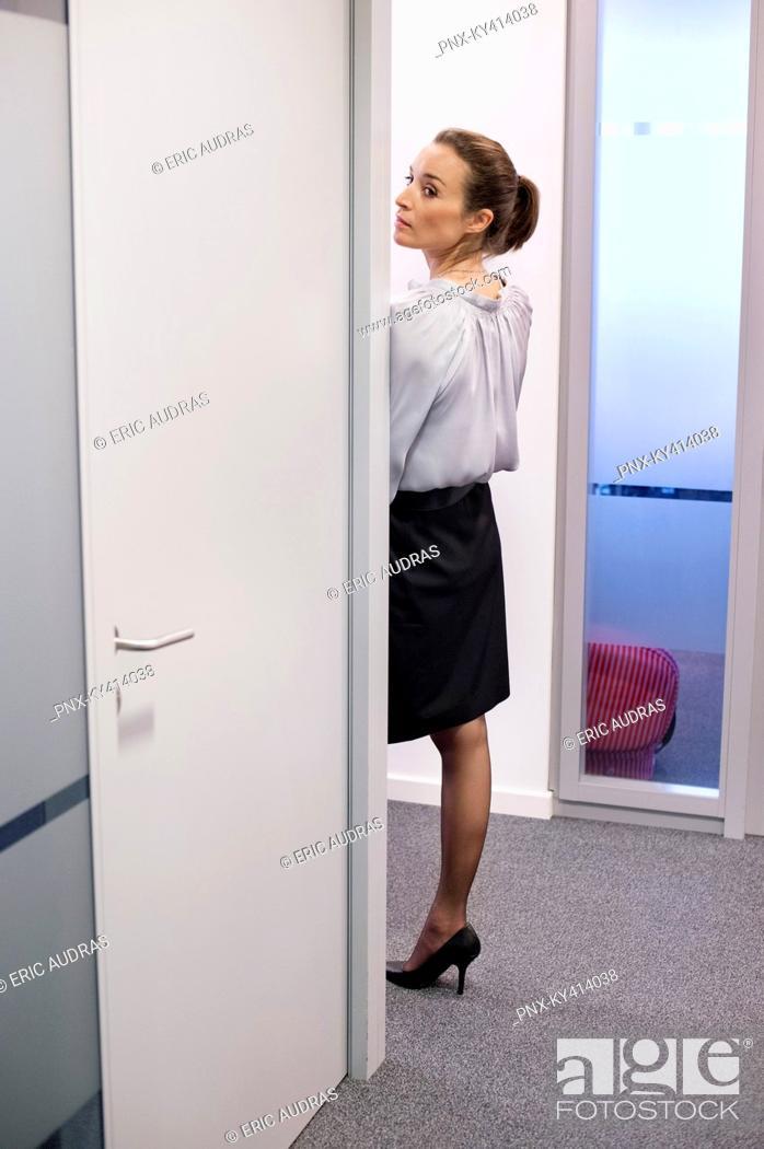 Stock Photo: Businesswoman peeking through a door in a corridor.