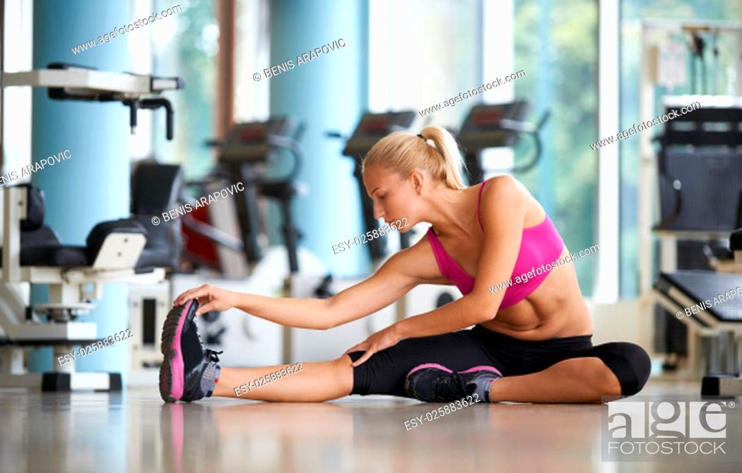 Stock Photo: Cute young woman stretching and warming up for her training at a gym.
