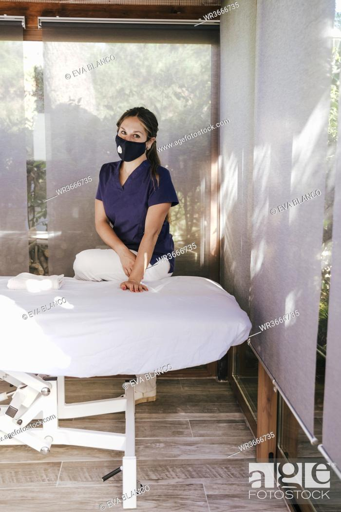 Stock Photo: Female therapist wearing mask standing by massage table in spa.