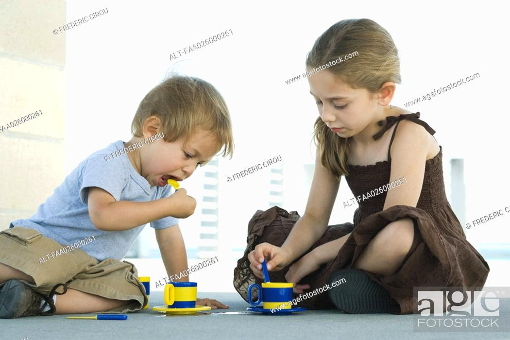 Stock Photo: Brother and sister sitting on the ground, playing with plastic teacups together.