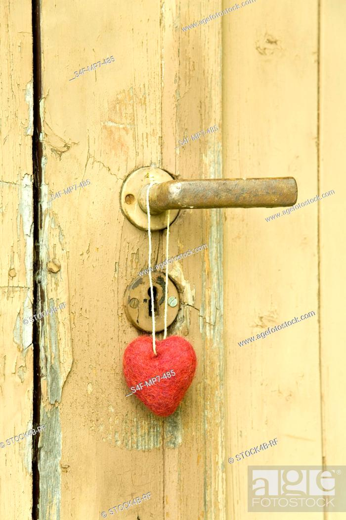 Stock Photo: Red heart hanging at door knob.