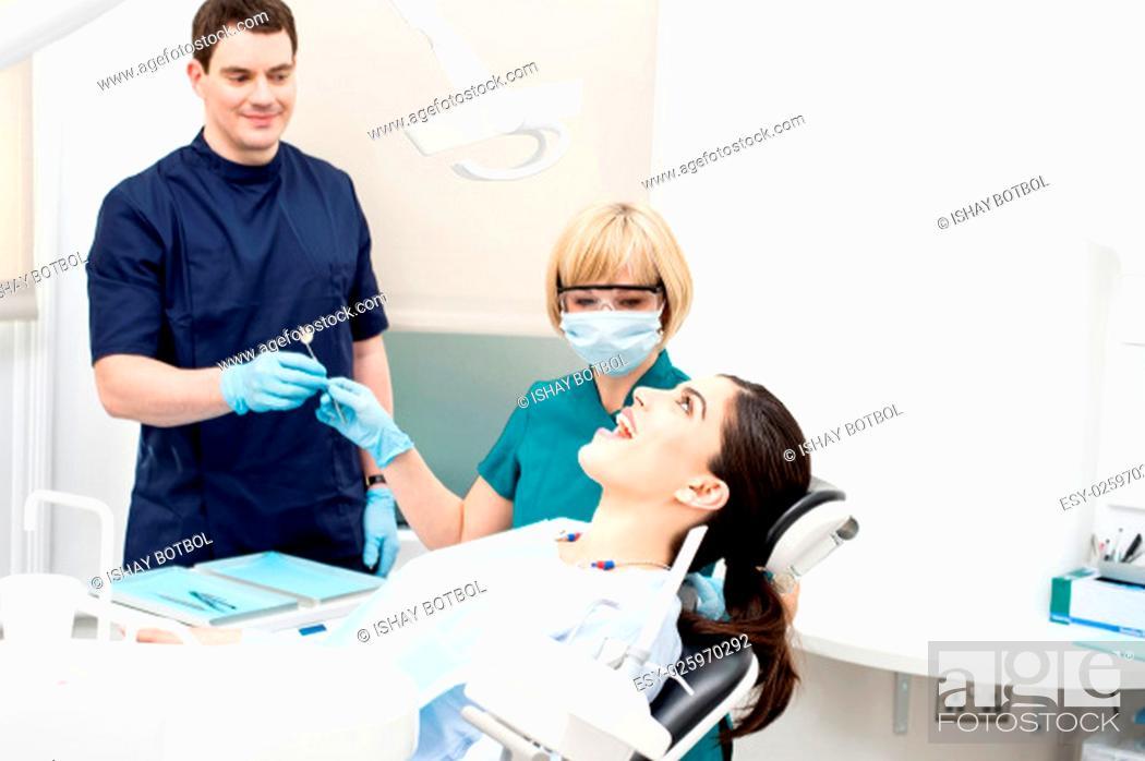 Stock Photo: Female dentist beginning the treatment.