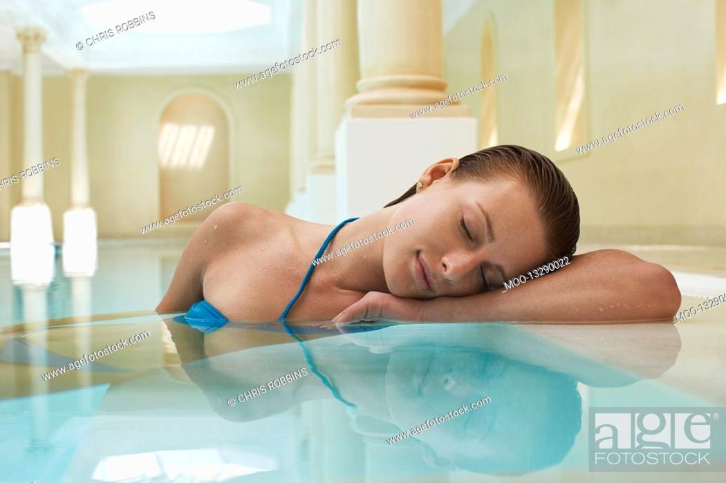 Stock Photo: Young woman with eyes closed leaning on edge of swimming pool portrait.