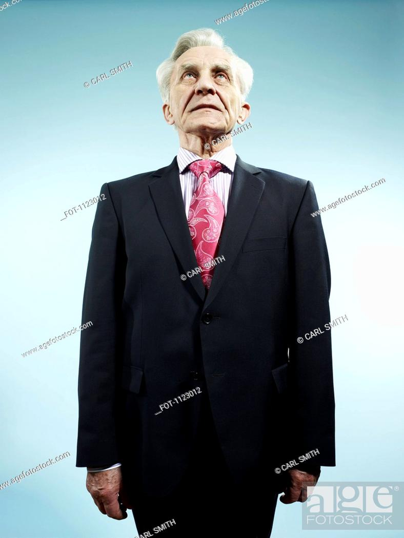 Stock Photo: An elegant senior man wearing a suit and pink paisley tie.