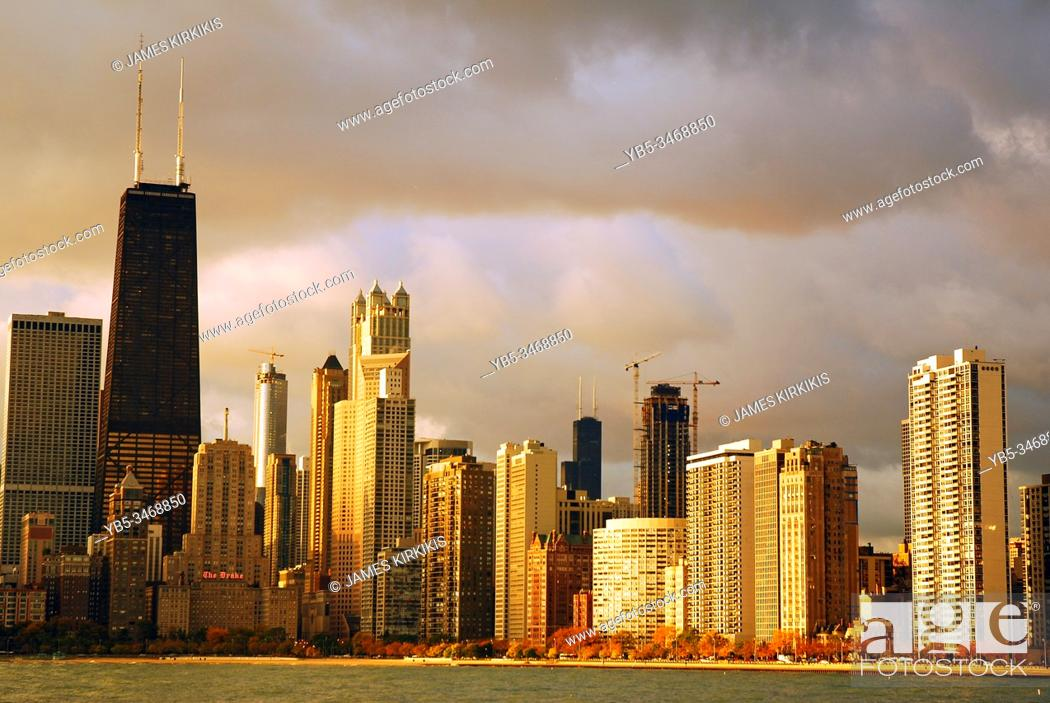 Stock Photo: A sun peaks through the overcast skies and illuminates the Chicago skyline.