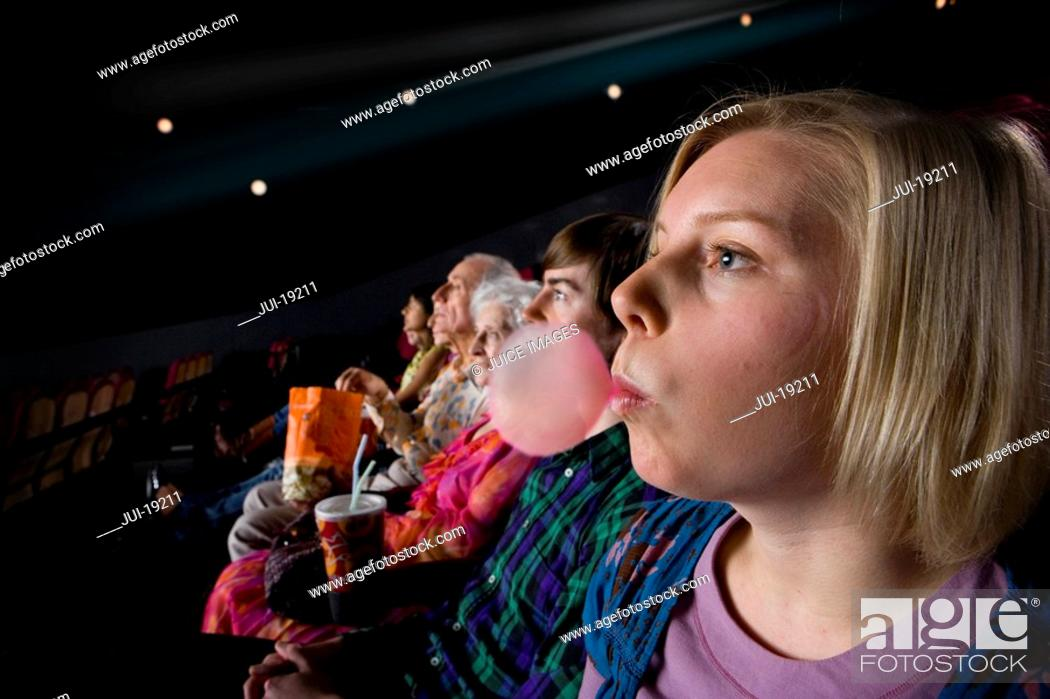 Stock Photo: Audience in cinema, woman blowing bubble with gum, side view.