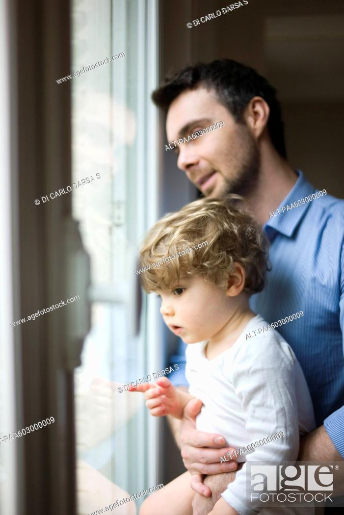 Stock Photo: Father and toddler son looking out window, portrait.