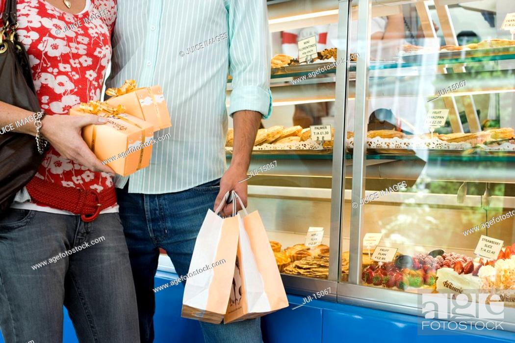 Stock Photo: Couple with gift boxes and shopping bags in bakery, mid section.