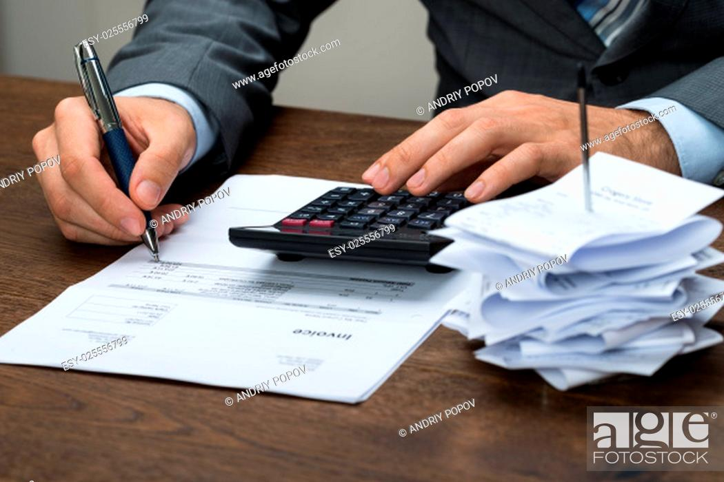 Stock Photo: Close-up Of Businessperson Calculating Financial Expenses In Office.