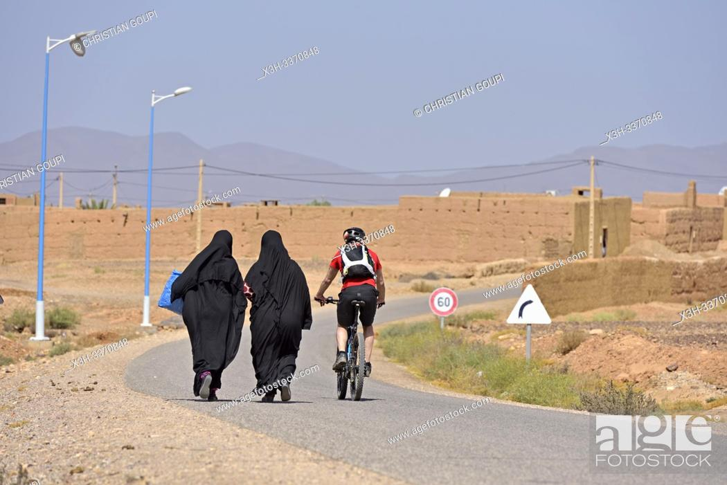 Stock Photo: man, mountain biking with electric assistance, overtaking two women dressed with abaya on a straight road through the reg, from Agdz to Zagora.