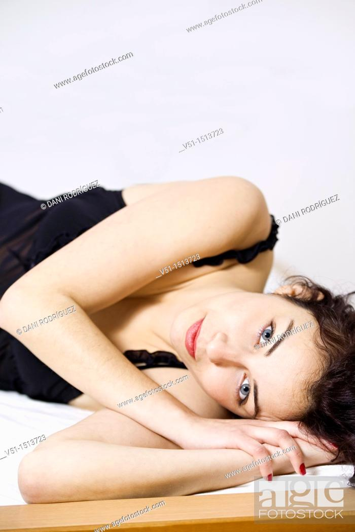 Stock Photo: Brunette woman with lingerie posing on bed.