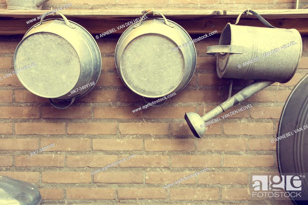 Stock Photo: Metal Watering Cans by Brick Wall in garden wood shelf.