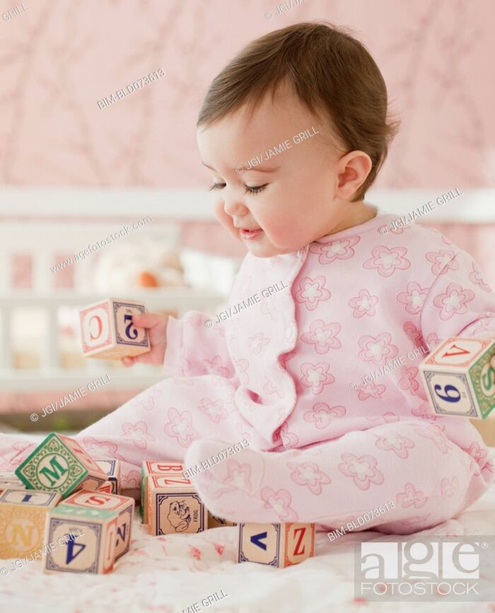 Stock Photo: Mixed race baby girl playing with alphabet blocks.