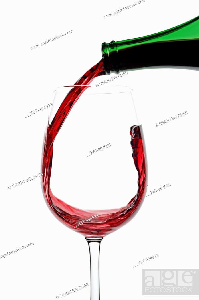 Stock Photo: Red Wine Being Poured into a Glass Against a White Background, Close Up.