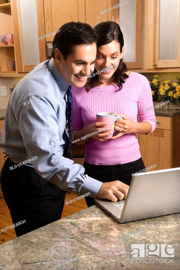 Stock Photo: MId-adult couple looking at laptop computer while drinking coffee in kitchen.