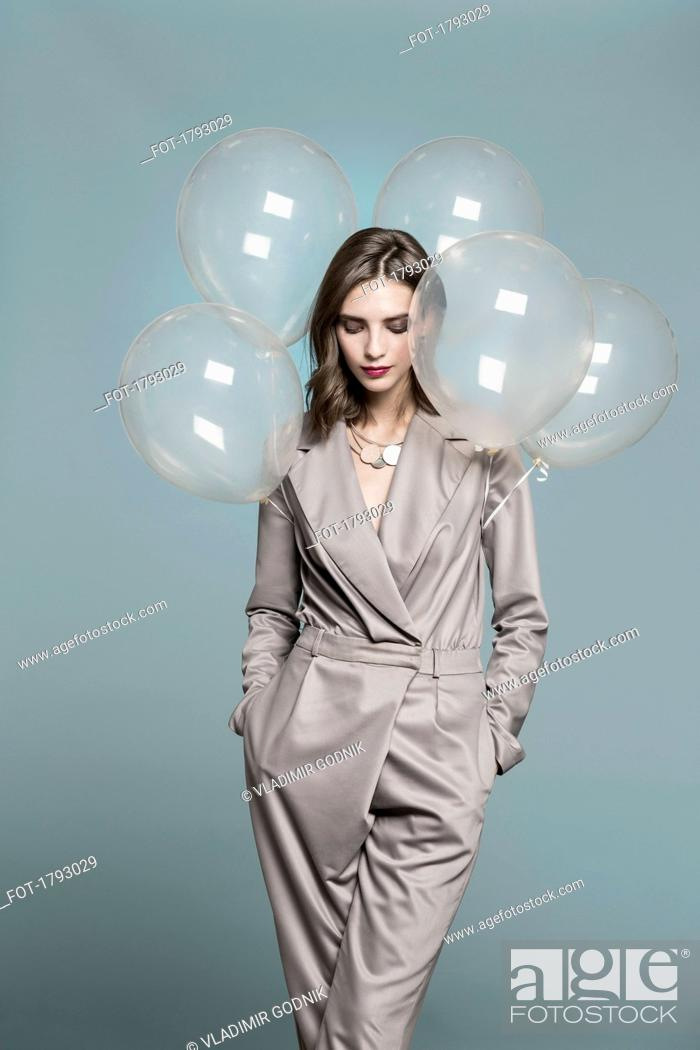 Stock Photo: Portrait of female fashion model standing with balloons against blue background.