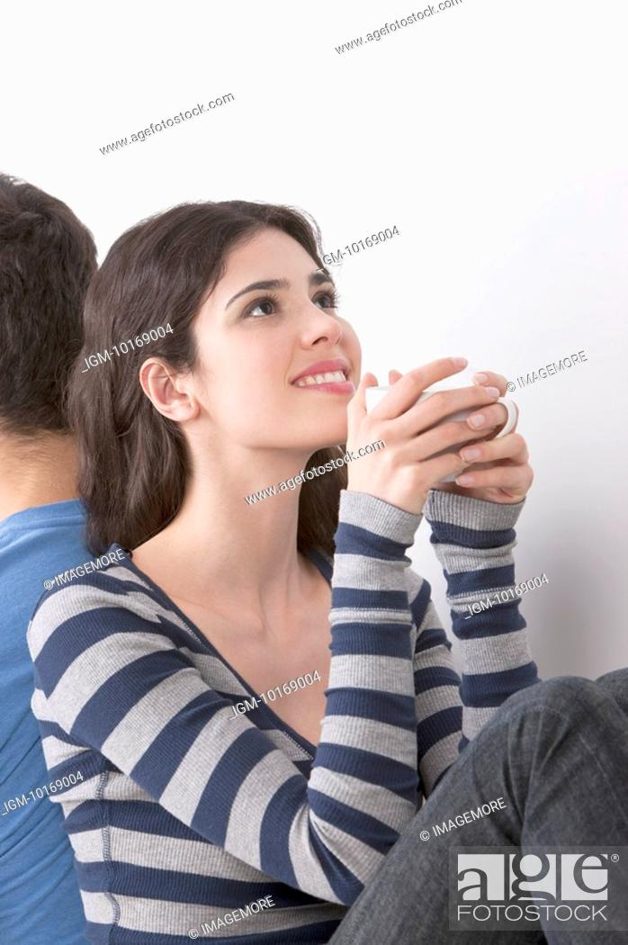 Stock Photo: Young woman sitting back to back with boyfriend, drinking coffee.