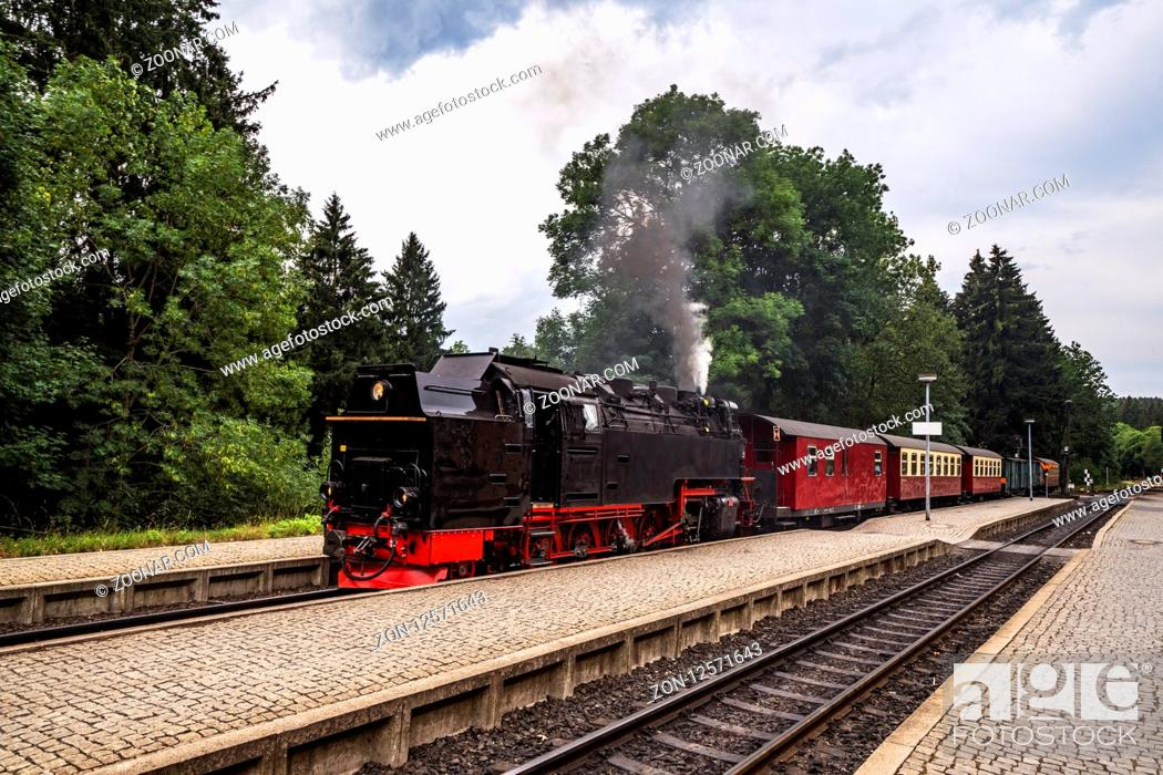 Stock Photo: Old steam locomotive leaving the train station with smoke coming out of the chimney.