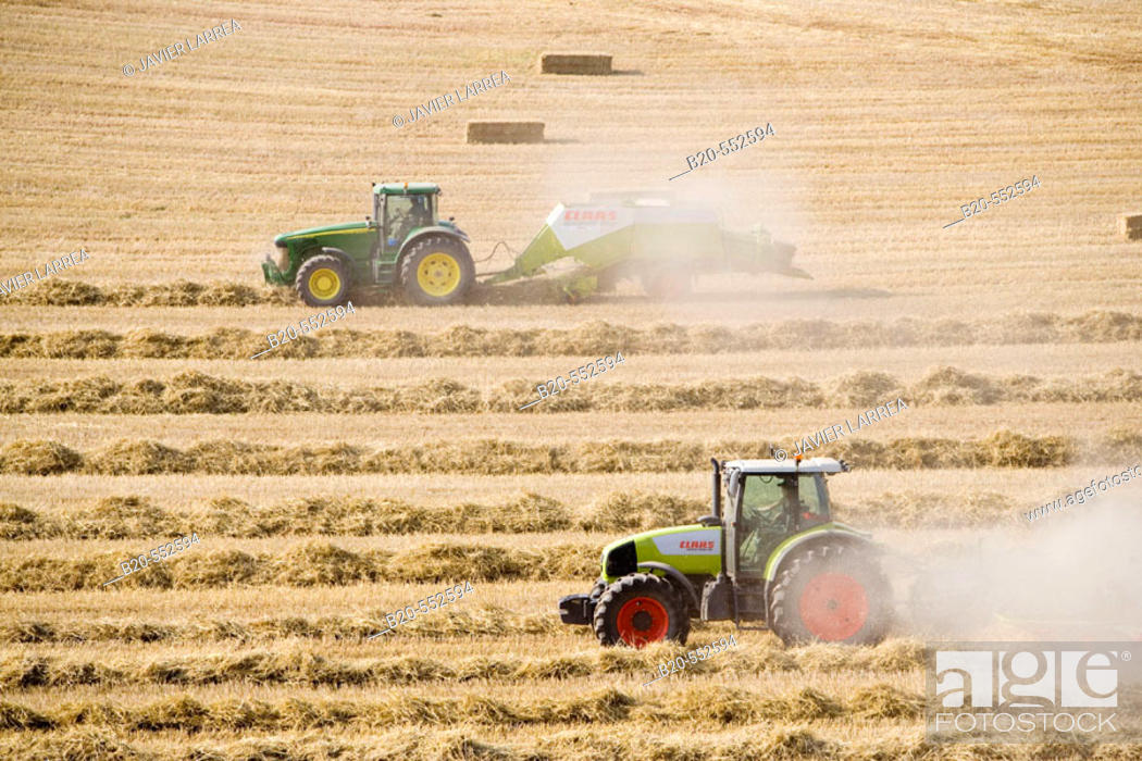 Stock Photo: Agricultural machinery. Windrower and Pick-up baler. Harvesting of cereals,  'Learza' estate. Near Estella, Navarre, Spain.