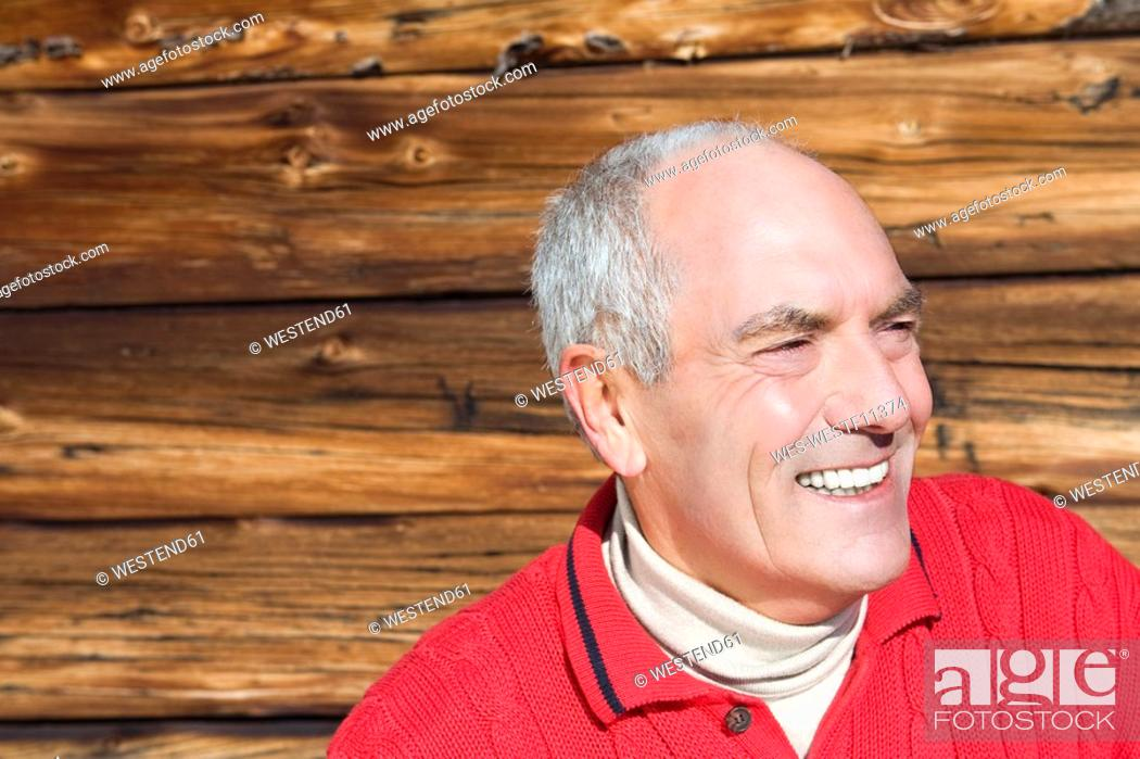 Stock Photo: Italy, South Tyrol, Seiseralm, Portrait of senior man in front of wooden wall, close-up.