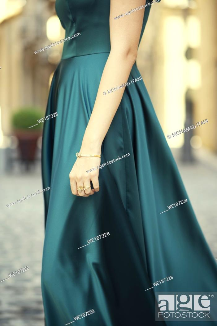 Stock Photo: Side view close up of a woman wearing green evening dress standing outdoors.