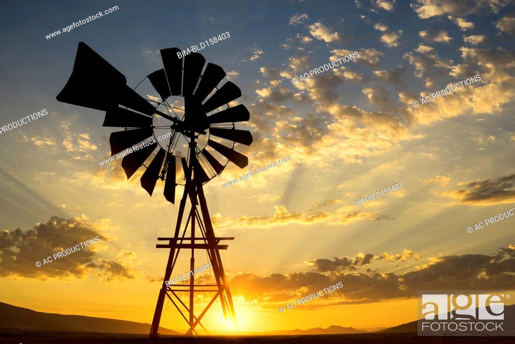 Stock Photo: Silhouette of windmill under dramatic sunset sky.