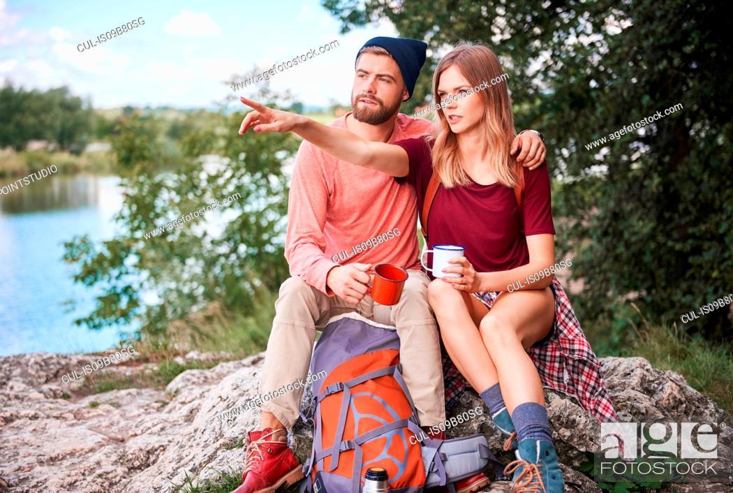 Photo de stock: Couple hiking, sitting on rocks holding enamel mugs, Krakow, Malopolskie, Poland, Europe.