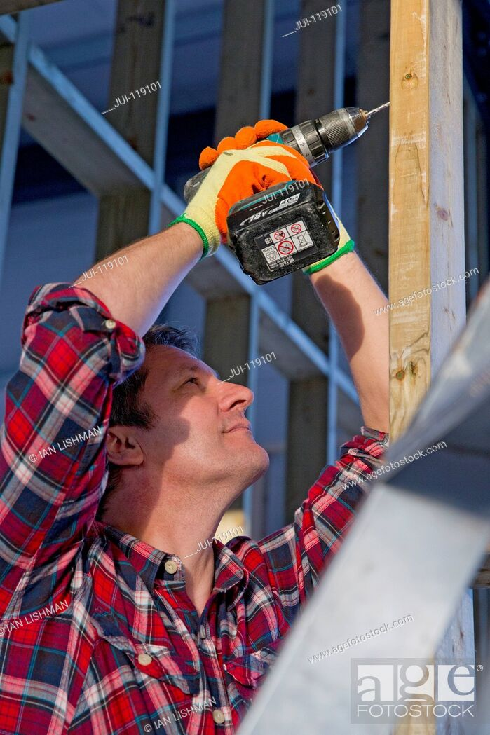 Stock Photo: Electrician drilling wooden frame on building construction site interior.