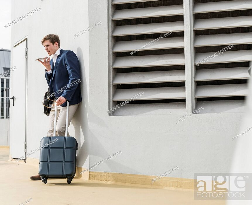 Stock Photo: Businessman with rolling suitcase using smartphone at parking garage.