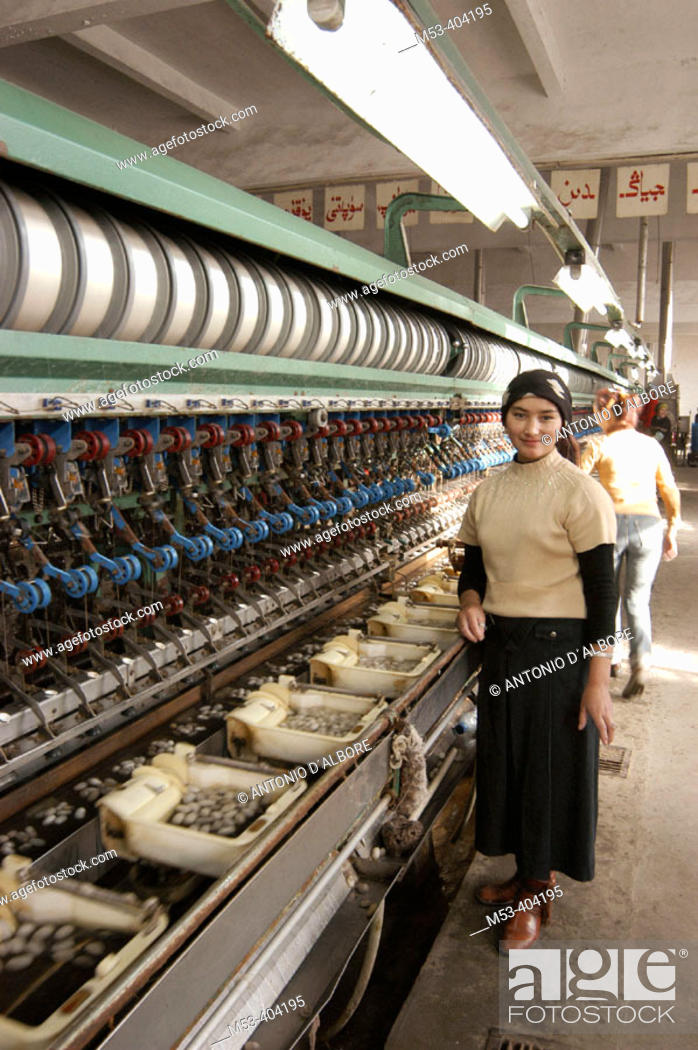 Stock Photo: Uighur woman operate a machine to spin silk from silkworms. Silk factory. Hotan (Hetian). Xinjiang Uyghur Autonomous Region. China.