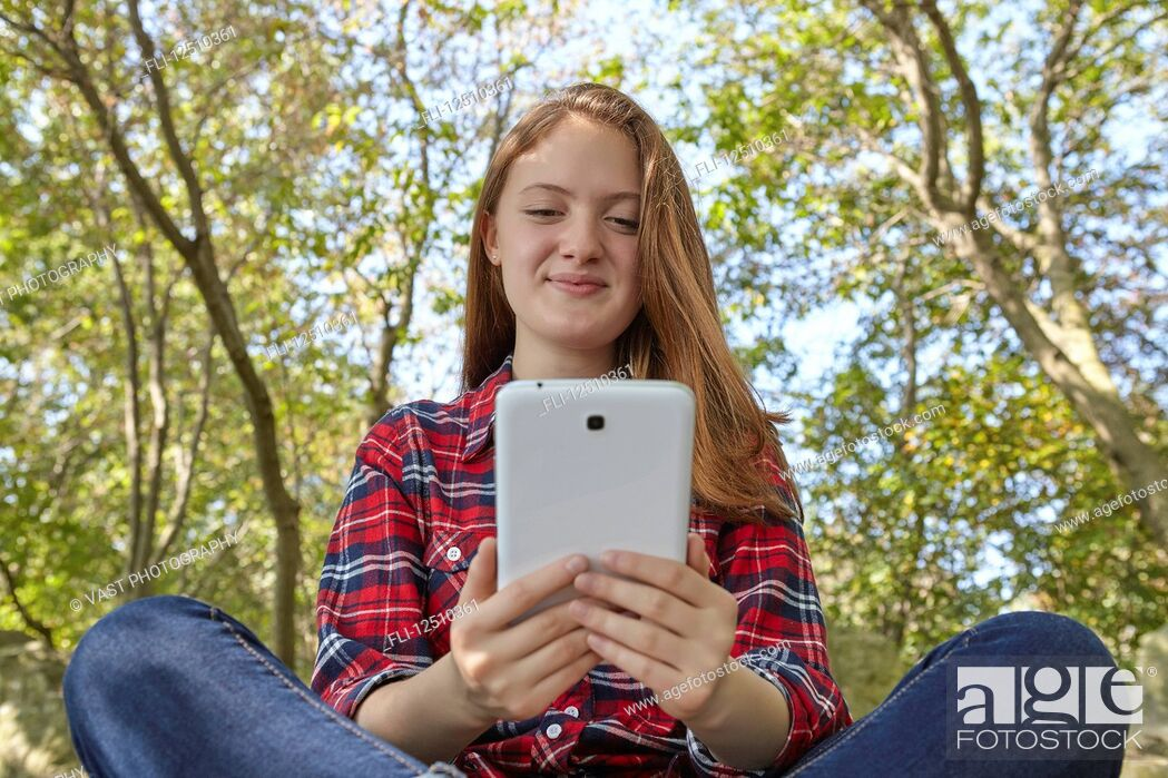 Stock Photo: A teenage girl wearing jeans and a plaid shirt sits on a boulder using her smart phone, Woodbine Beach; Toronto, Ontario, Canada.