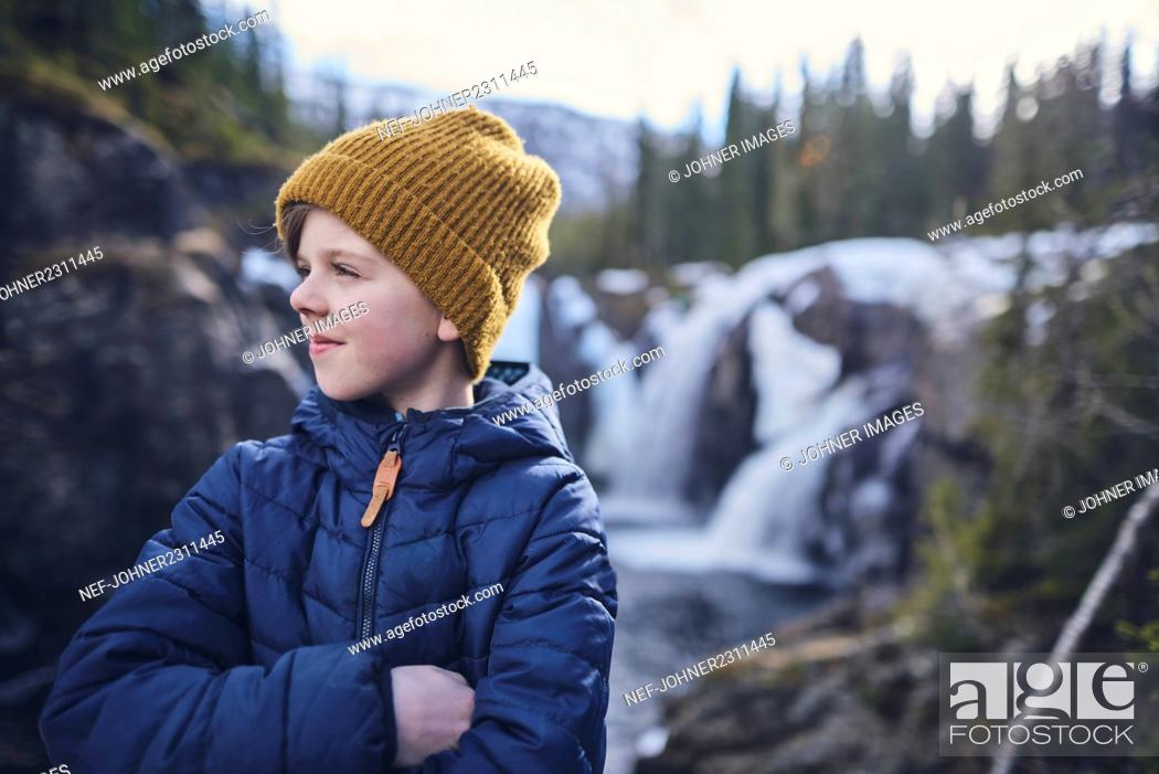 Photo de stock: Portrait of boy with waterfall in background.