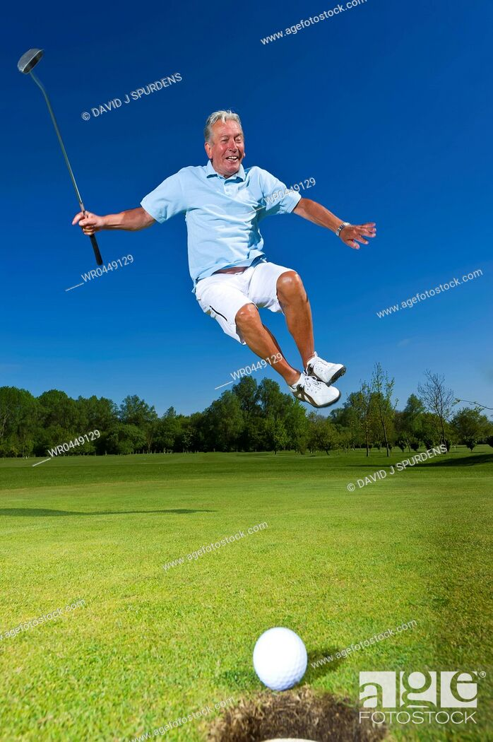 Stock Photo: A senior citizen leaps for joy as golf ball heads towards success.