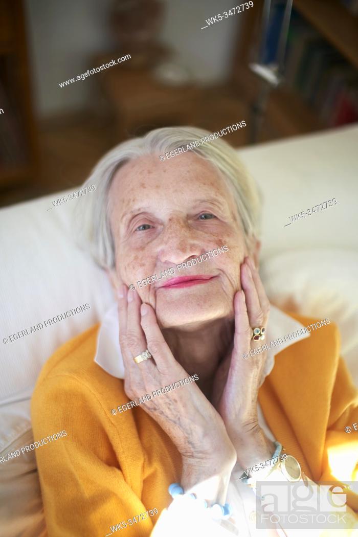Stock Photo: Senior woman relaxing at sofa.