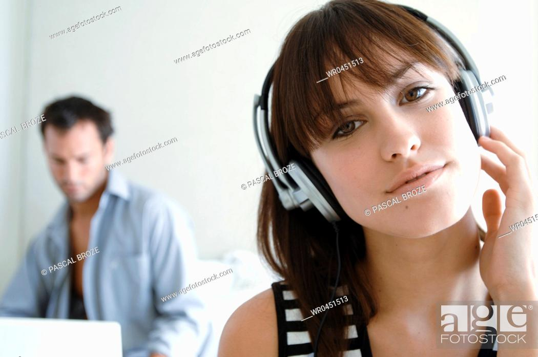 Imagen: Close-up of a young woman listening to music with a young man using a laptop in the background.