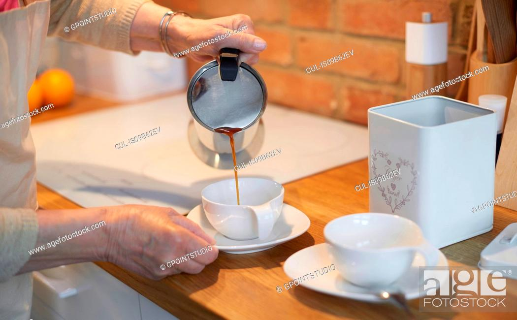 Stock Photo: Senior adult woman pouring coffee into cups.