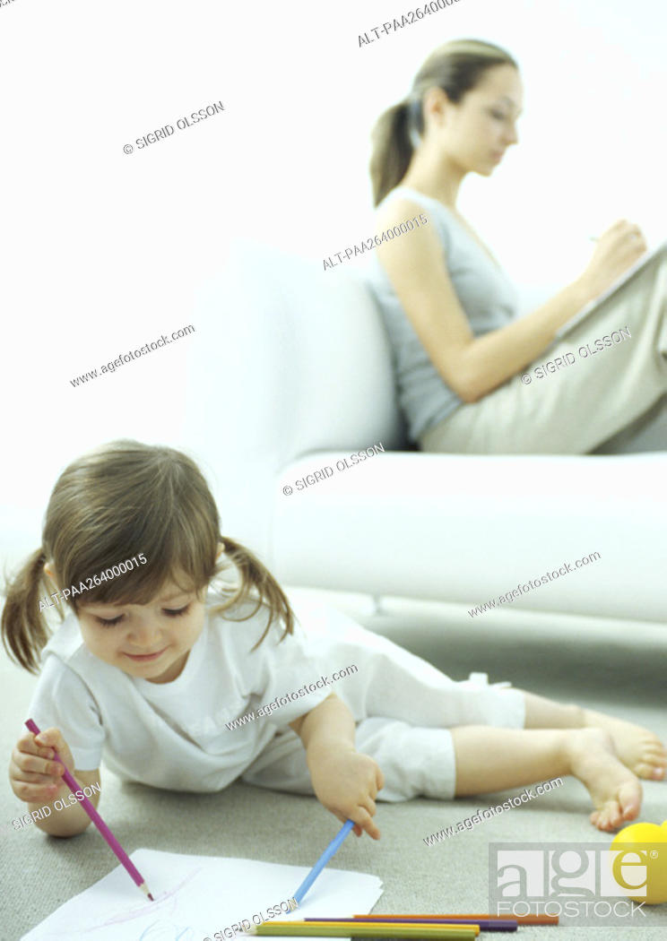 Stock Photo: Little girl lying on floor coloring, young woman sitting behind her on couch writing with knees up.