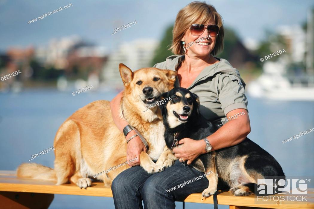 Stock Photo: a woman embracing her two dogs by waterfront, victoria, vancouver island, british columbia, canada.