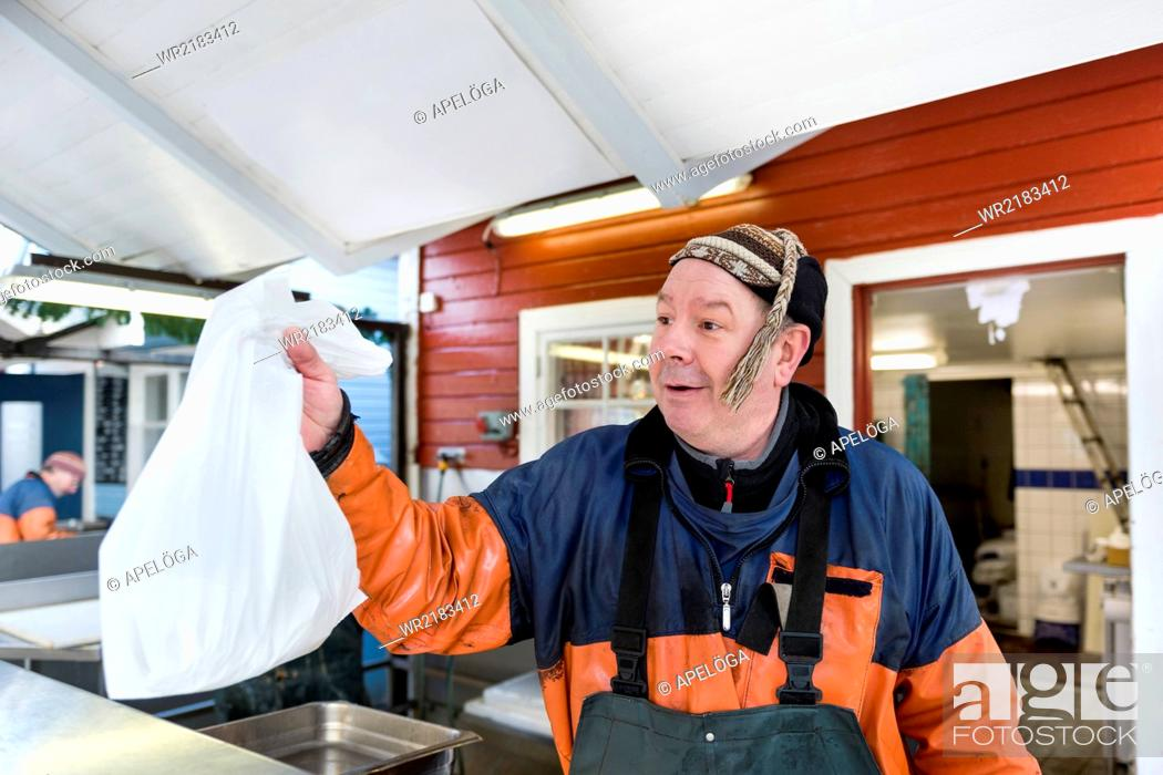 Stock Photo: Mature fisherman giving plastic bag of fish at fishing industry.