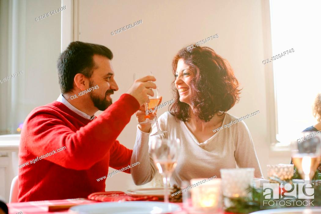 Stock Photo: Couple toasting at family Christmas party.