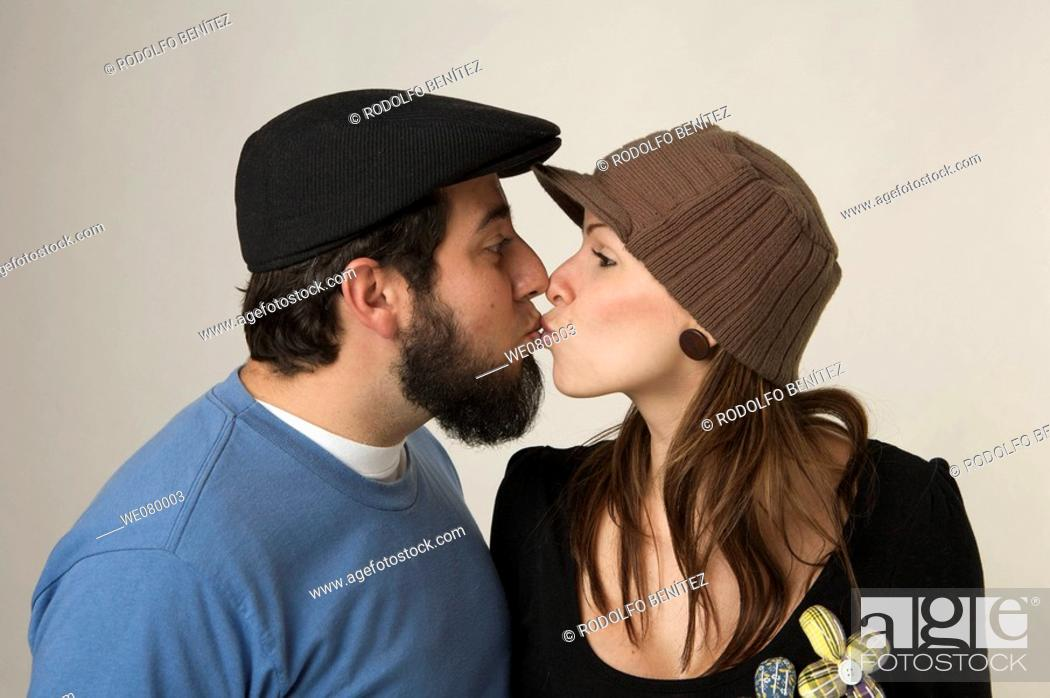 Stock Photo: Young trendy couple holding kissing in a studio setting.