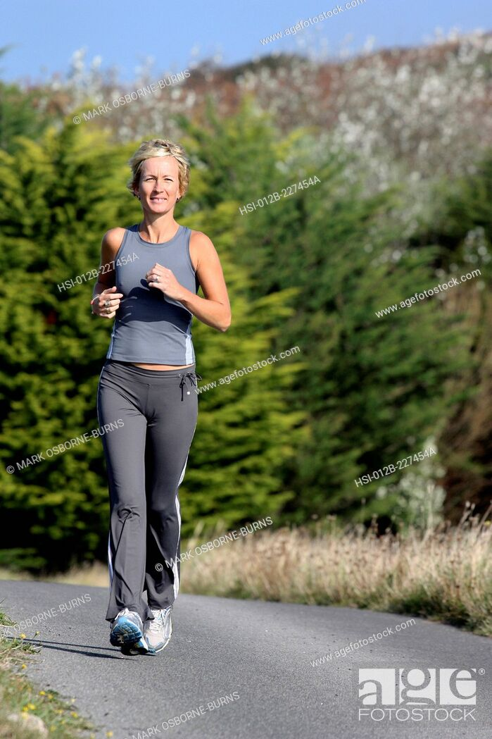 Stock Photo: Blonde woman outdoors. Jogging along country road.