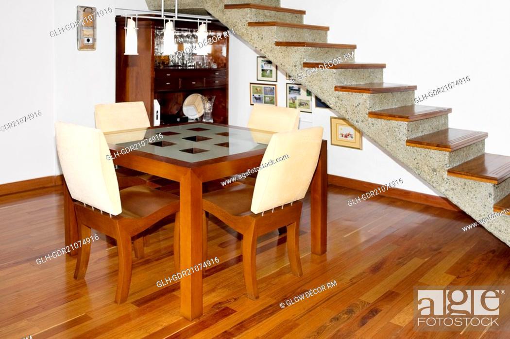 Photo de stock: Dining table near a staircase.