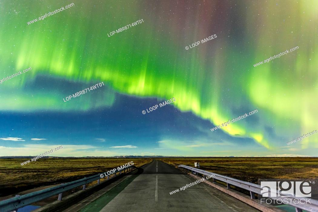 Stock Photo: Aurora Borealis over a road near Vik in Southern Iceland.