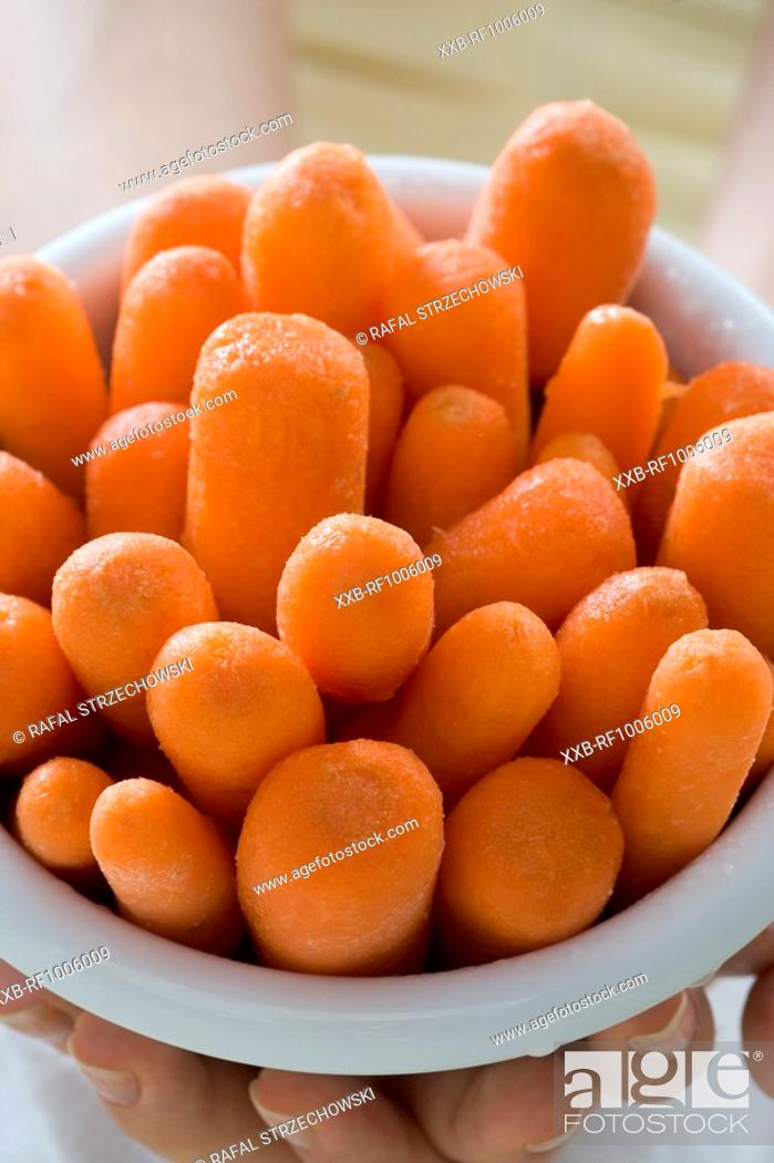 Stock Photo: close-up of a woman holding bowl with carrots.