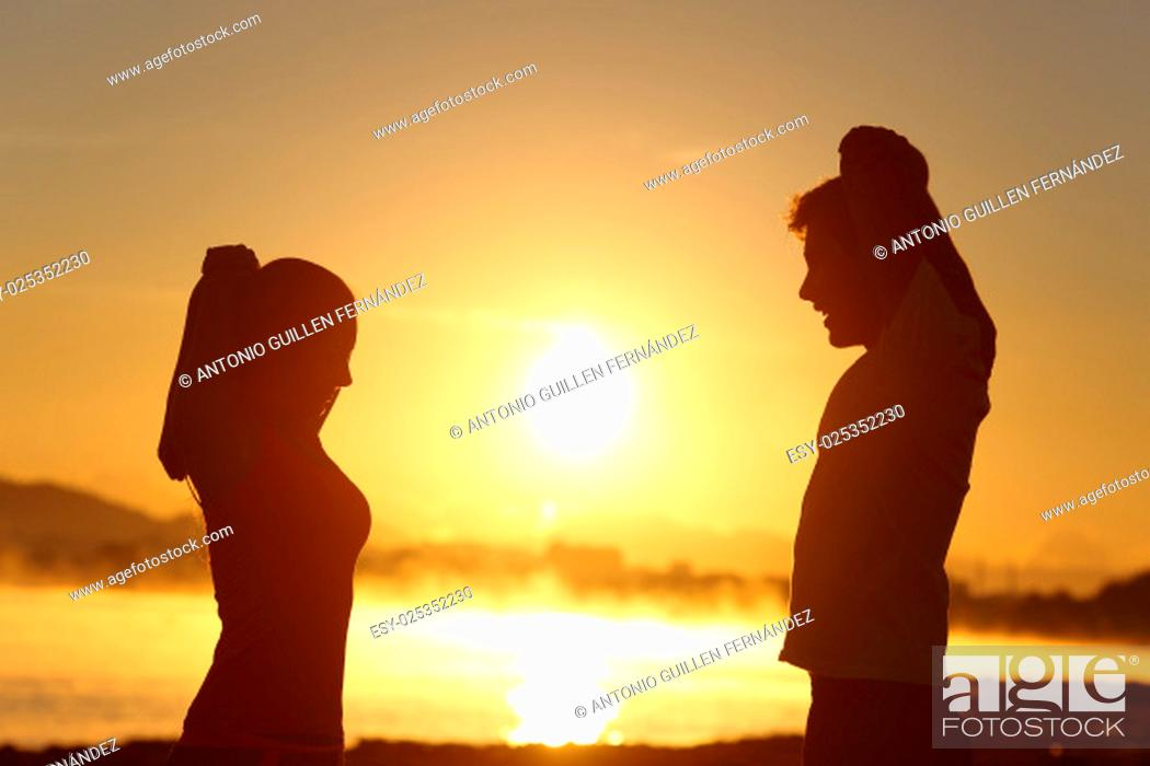 Stock Photo: Silhouette of a fitness couple stretching at sunrise with the sun in the background.