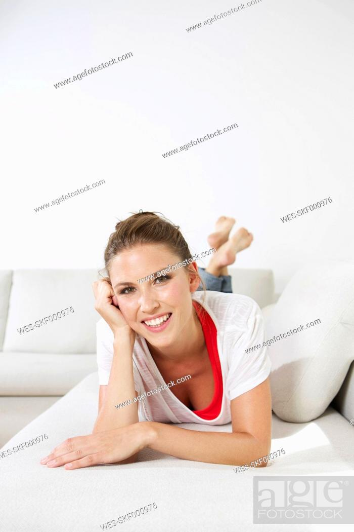 Stock Photo: Germany, Berlin, Young woman lying on couch, smiling.