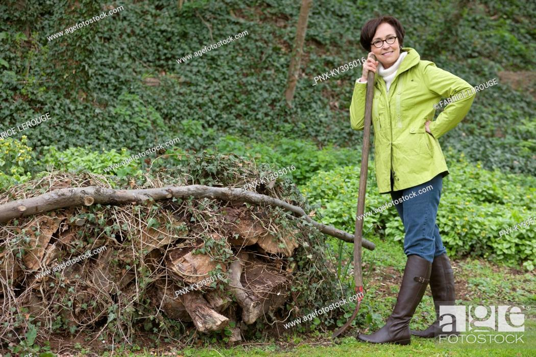 Stock Photo: Woman standing with a shovel near a heap of rubbish.