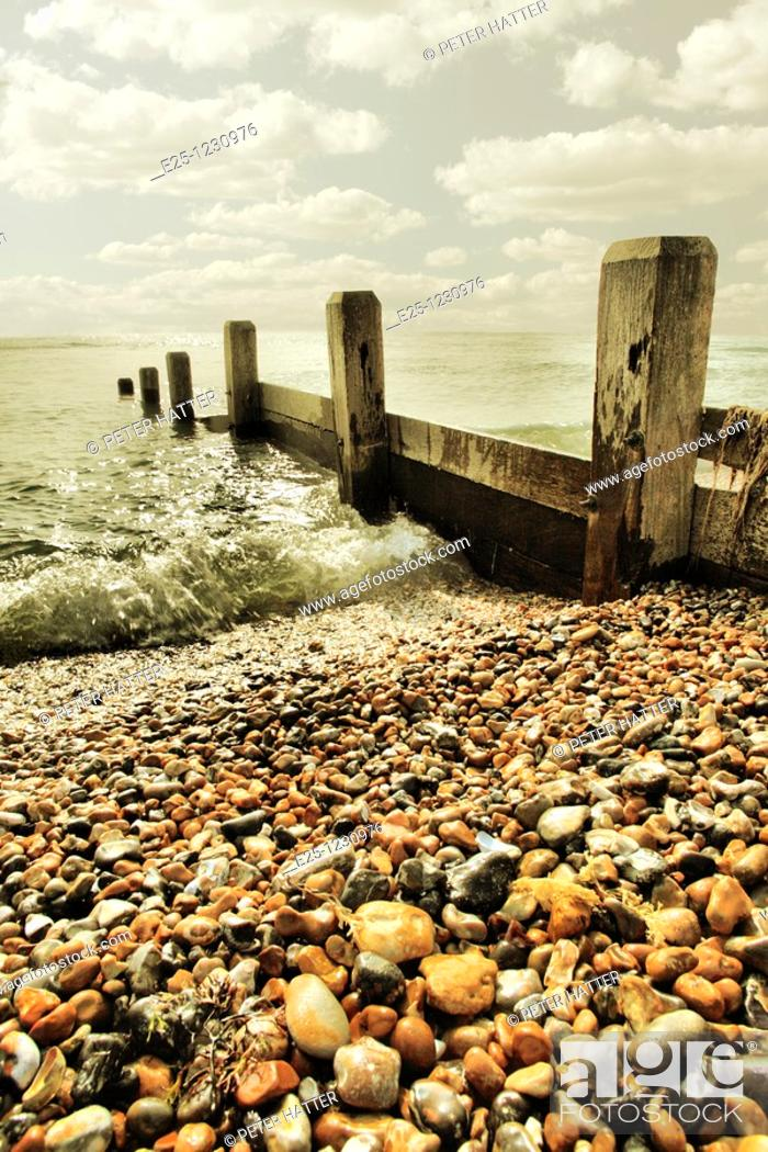 Stock Photo: An old breakwater sea defence on a pebble beach with a small wave from a calm sea breaking up the beach.  Location: Sussex UK.