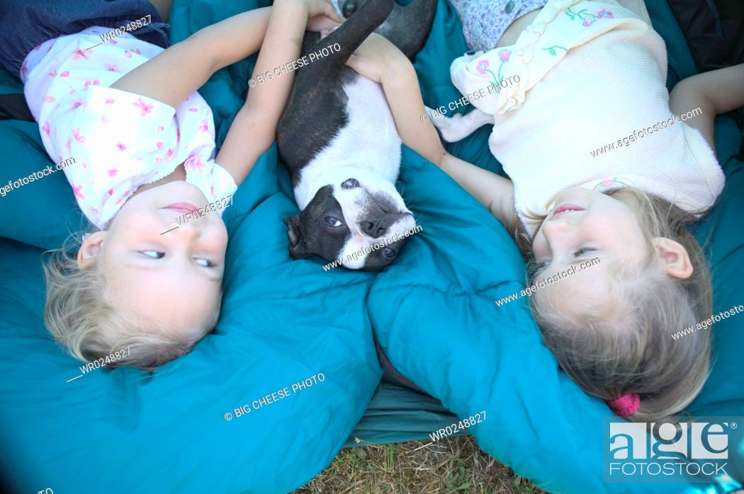 Stock Photo: Young sisters and their dog on sleeping bags.